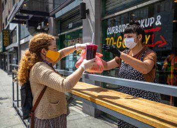 Woman Wearing Homemade Mask Picks Up Food at Restaurant During Covid-19 Lockdown