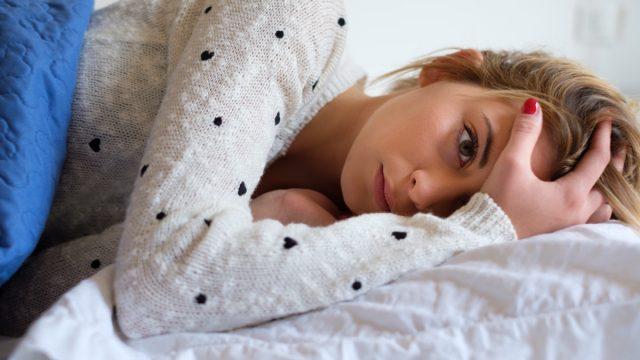 Woman feeling bad and trying to sleep