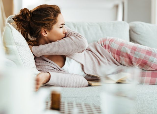 woman coughing into elbow while lying down on sofa in the living room.