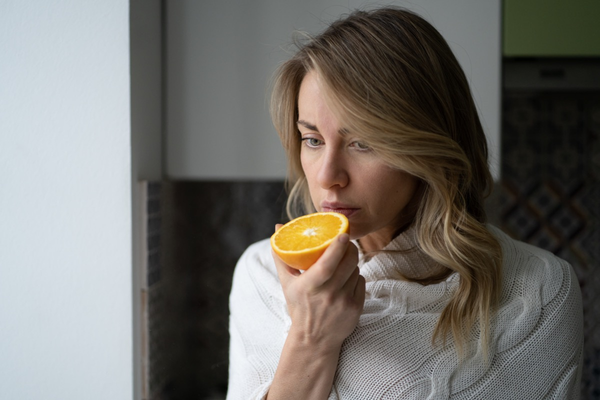 woman trying to sense smell of half fresh orange, has symptoms of Covid-19