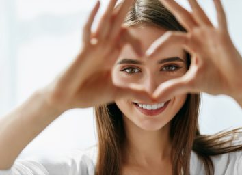 Happy Woman Holding Heart Shaped Hands Near Eyes. Closeup Of Smiling Girl With Healthy Skin Showing Love Sign