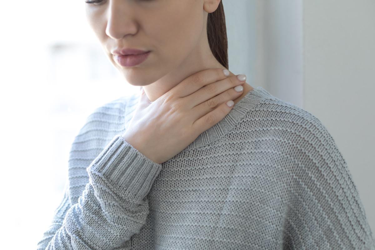 Woman touching her throat.