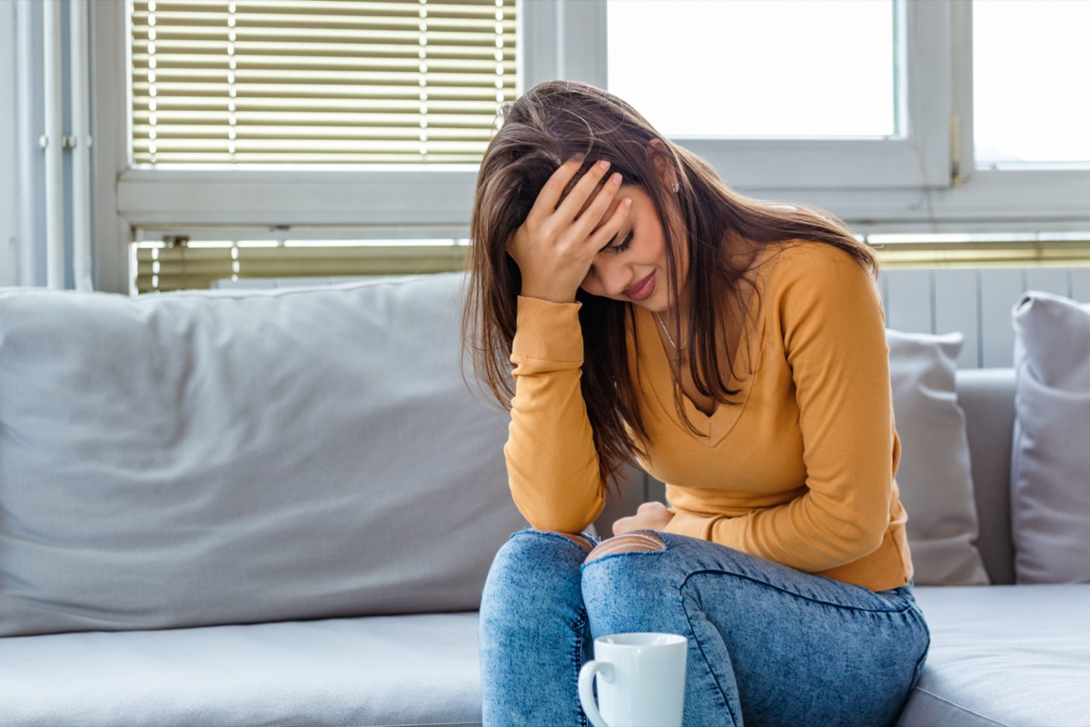 woman suffering from abdominal pain while sitting on bed at home. Young woman suffering from abdominal pain at home. Gynecology concept. Young woman in pain lying on couch at home