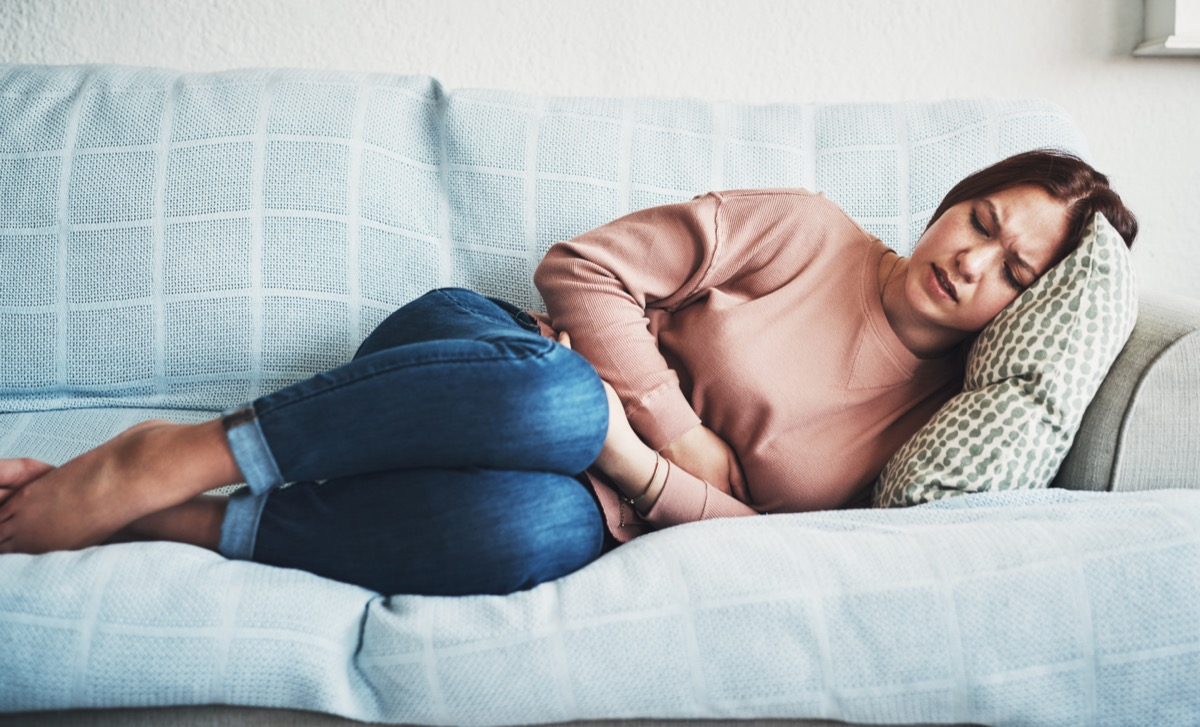 Woman lying on sofa and suffering from stomach pain.