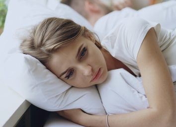 Depressed young woman lying in bed and feeeling upset.
