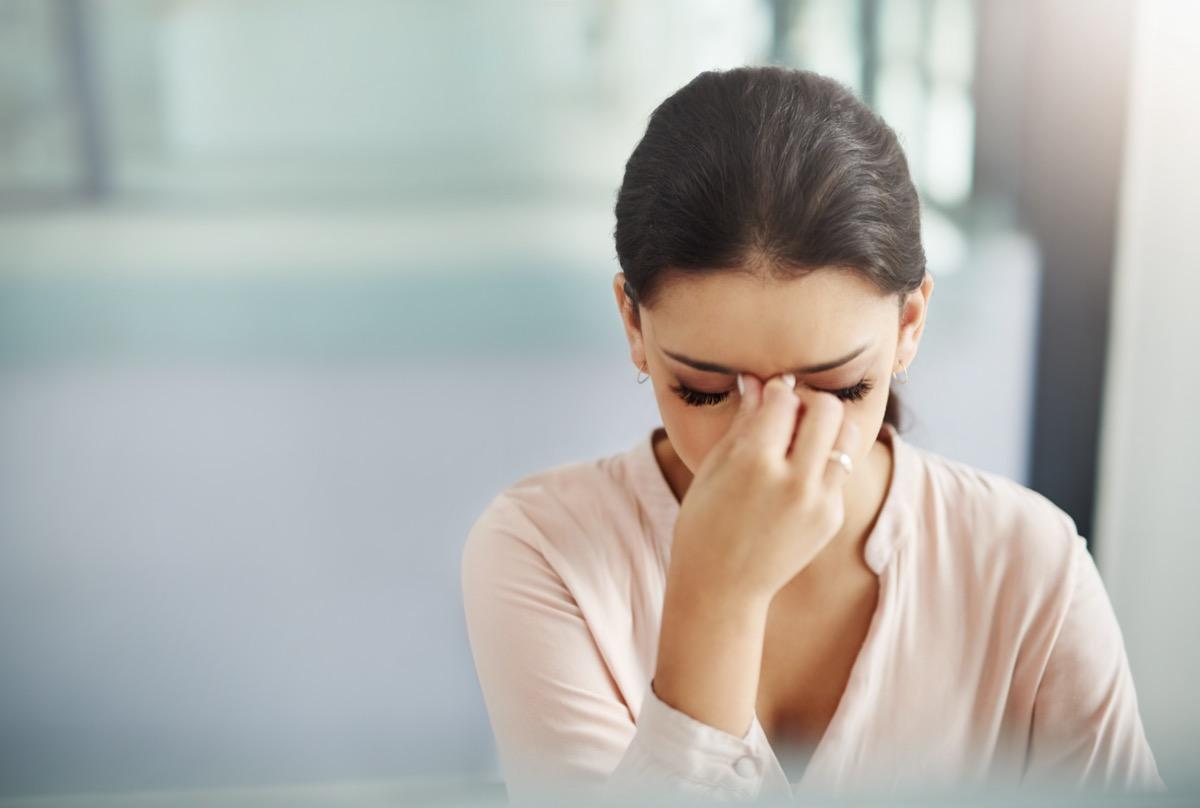 A businesswoman rubbing her eyes.