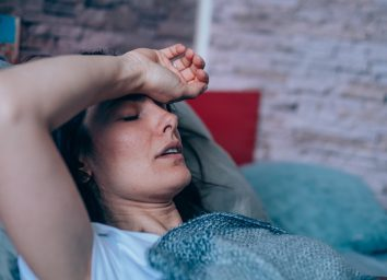 Sick young woman lying in the bed covered with blanket