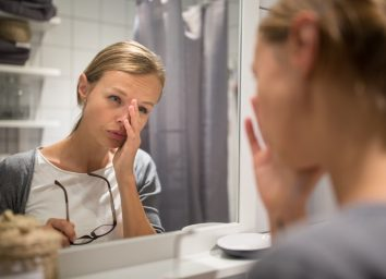 Groggy, young woman yawning in front of her bathroom mirror