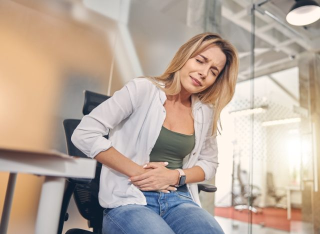 Upset young woman suffering from stomachache in office