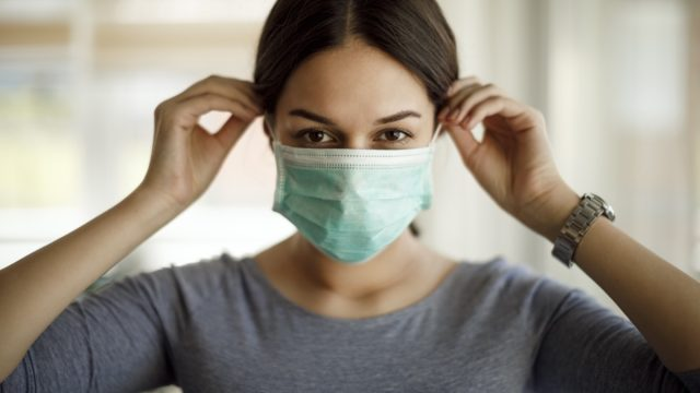 Woman putting on a protective mask