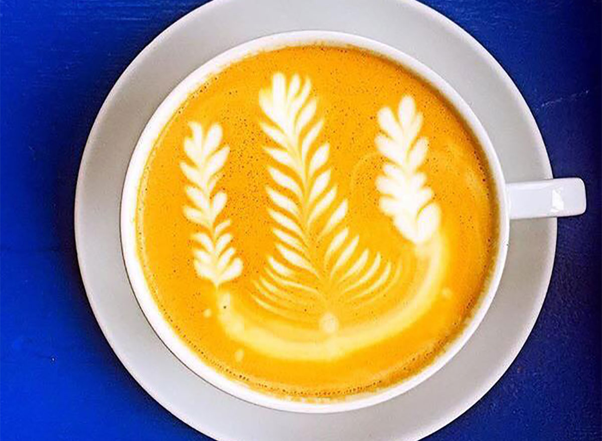 latte in mug with latte art on blue background