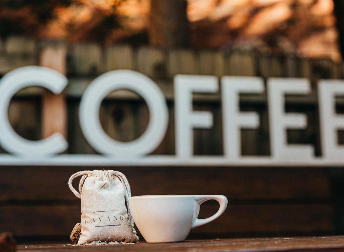 bag of coffee beans and coffee mug in front of decorative sign