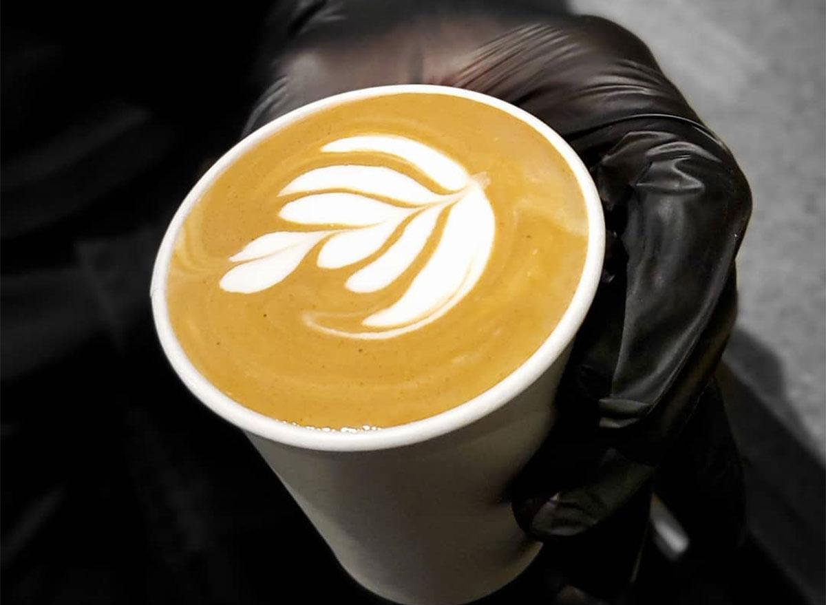 black gloved hands holding latte