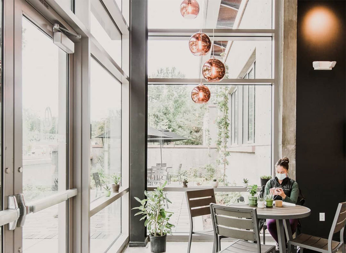 woman sitting at indoor dining cafe table