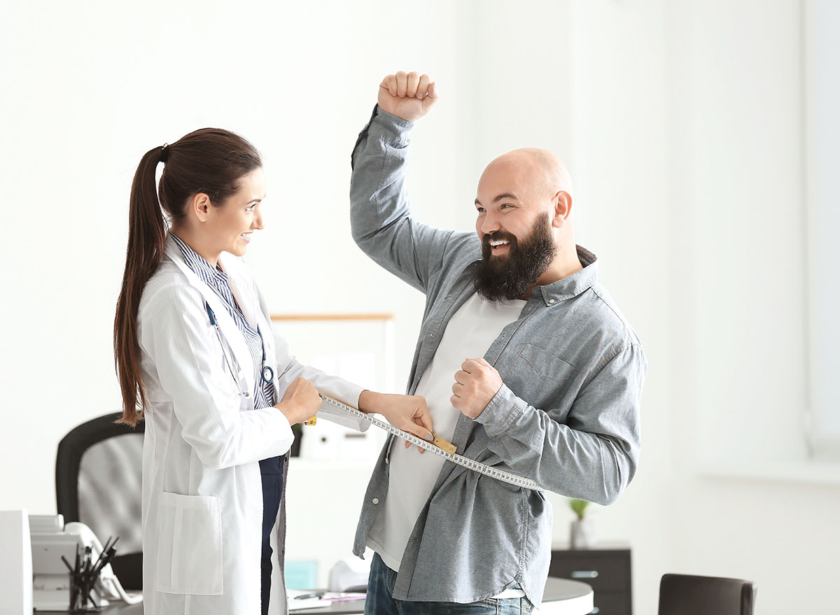 female doctor checking male patient weight