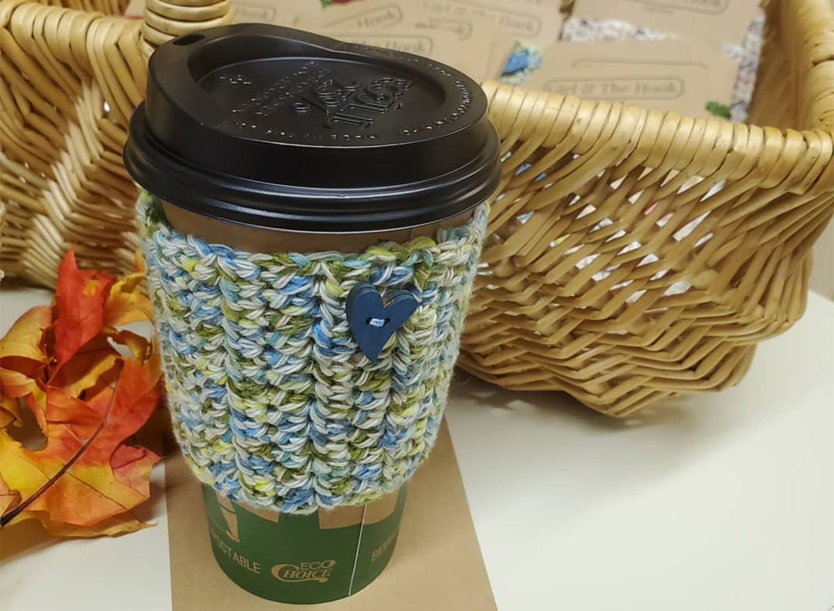 coffee with knitted sleeve in front of basket