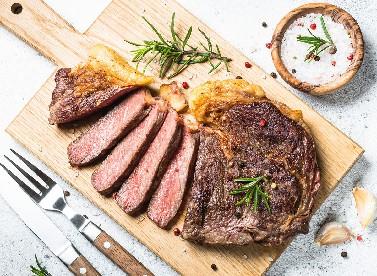 sliced steak on cutting board with fork and knife