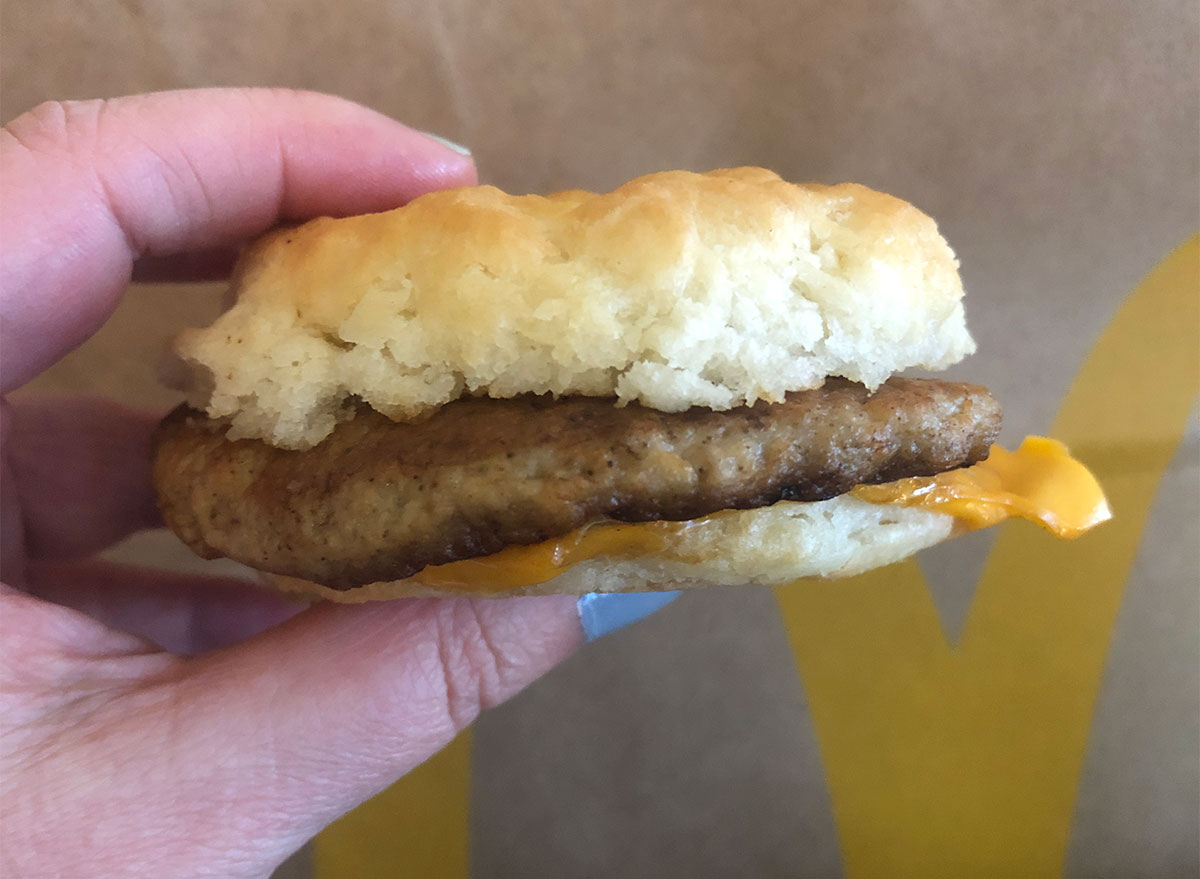 hand holding mcdonalds sausage and cheese biscuit