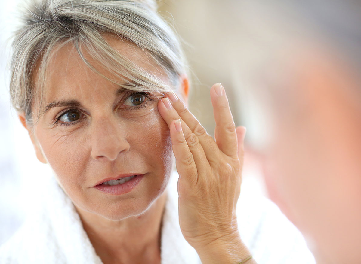 older woman touching wrinkles on face