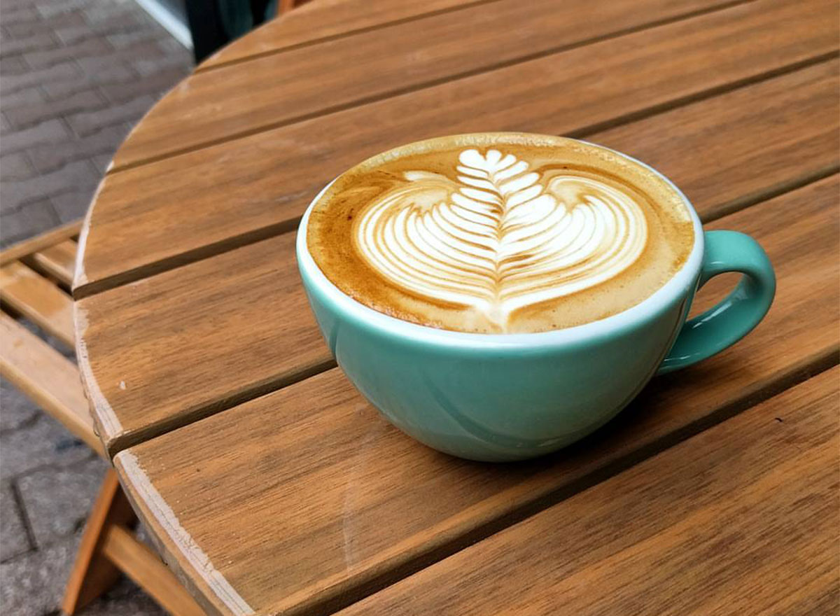 mug with latte art on wooden picnic table