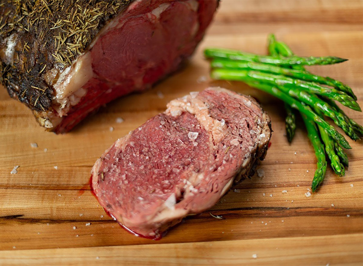 slice of prime rib on cutting board with asparagus and flaky salt