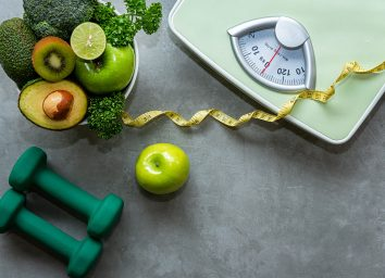 scale with weights measuring tape and bowl of healthy foods