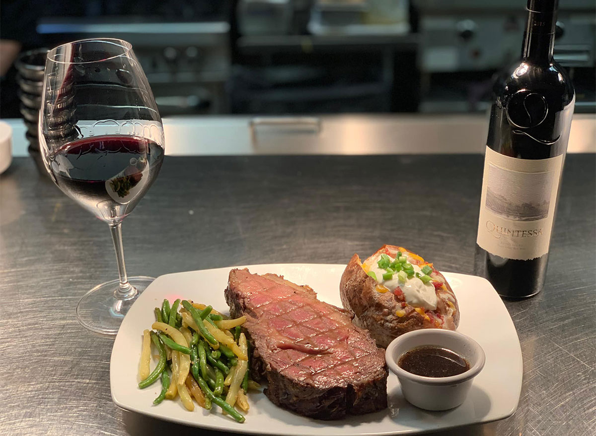 steak and baked potato with glass of wine
