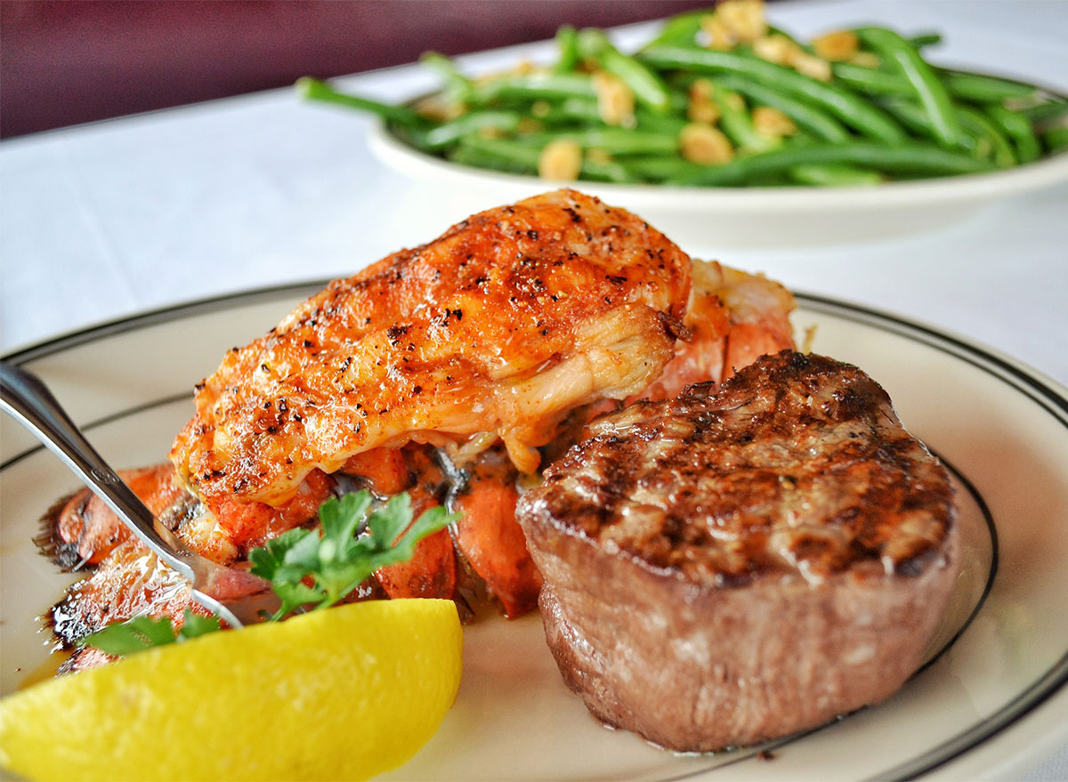 steak with lobster tail and lemon wedge