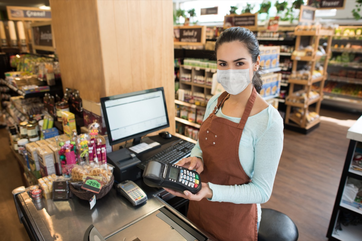 Cashier wearing a face mask at the grocery shop and getting a card payment