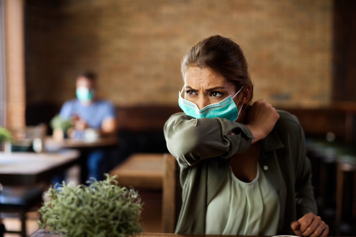 Woman with face mask sneezing into elbow while sitting in a cafe.