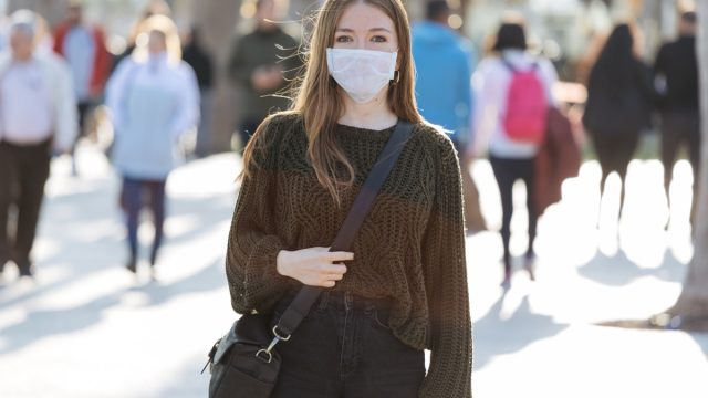 Woman wearing face mask on a busy street.