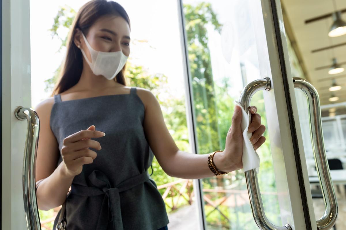 Woman's hand with tissue paper to push restaurant door open.