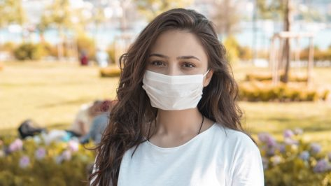Woman in protective sterile medical mask on her face, smiling.
