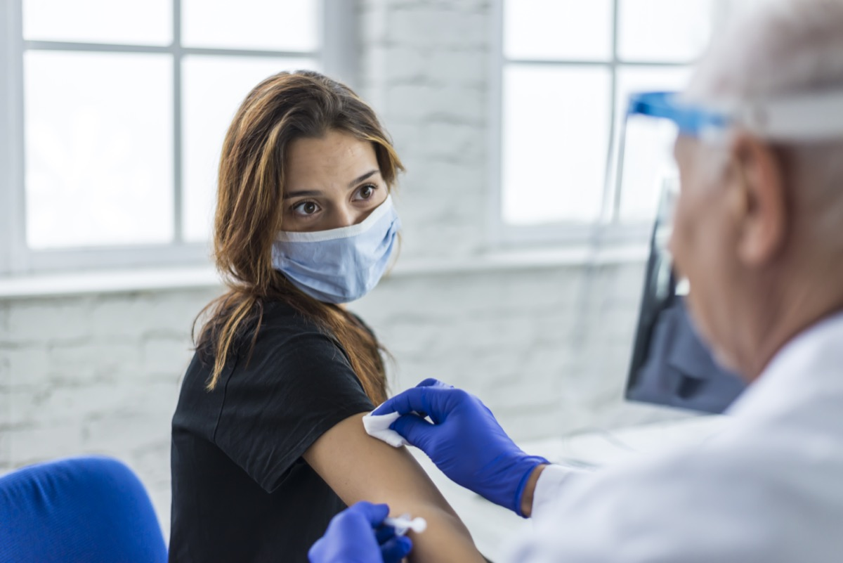 Young woman taking a vaccine from her doctor.