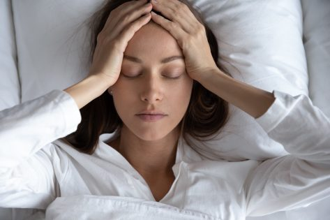Depressed woman suffering from headache, lying in bed