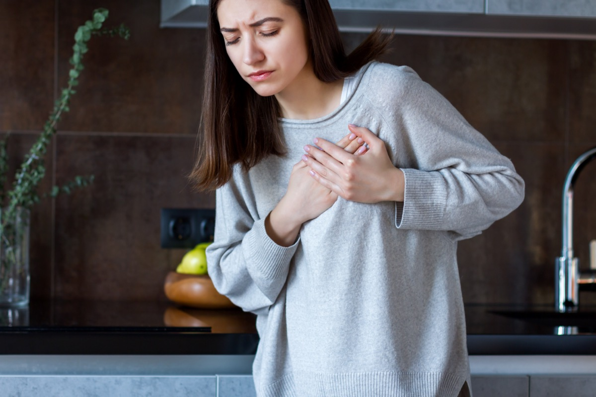 Woman in gray clothes keeps hands on her chest.