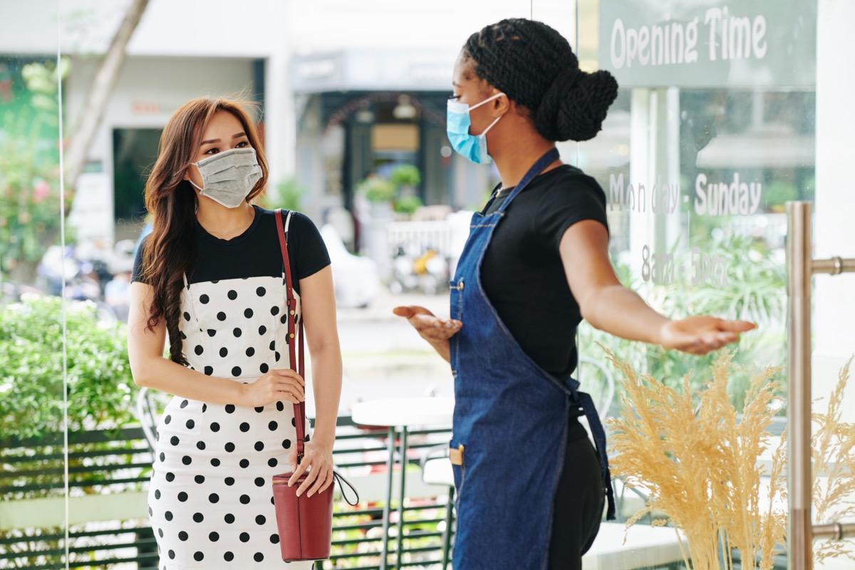 Waitress in medical mask inviting customer