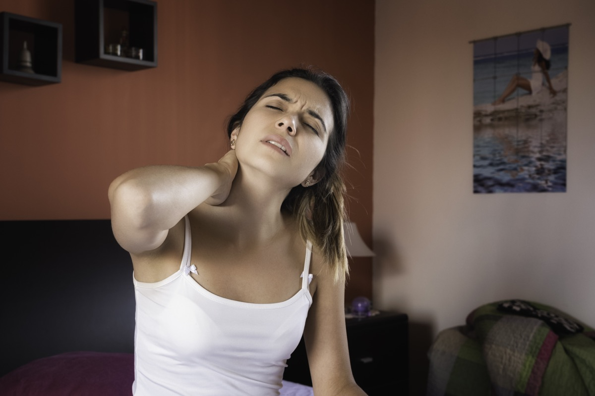 Woman with pain in her neck while sitting on bed