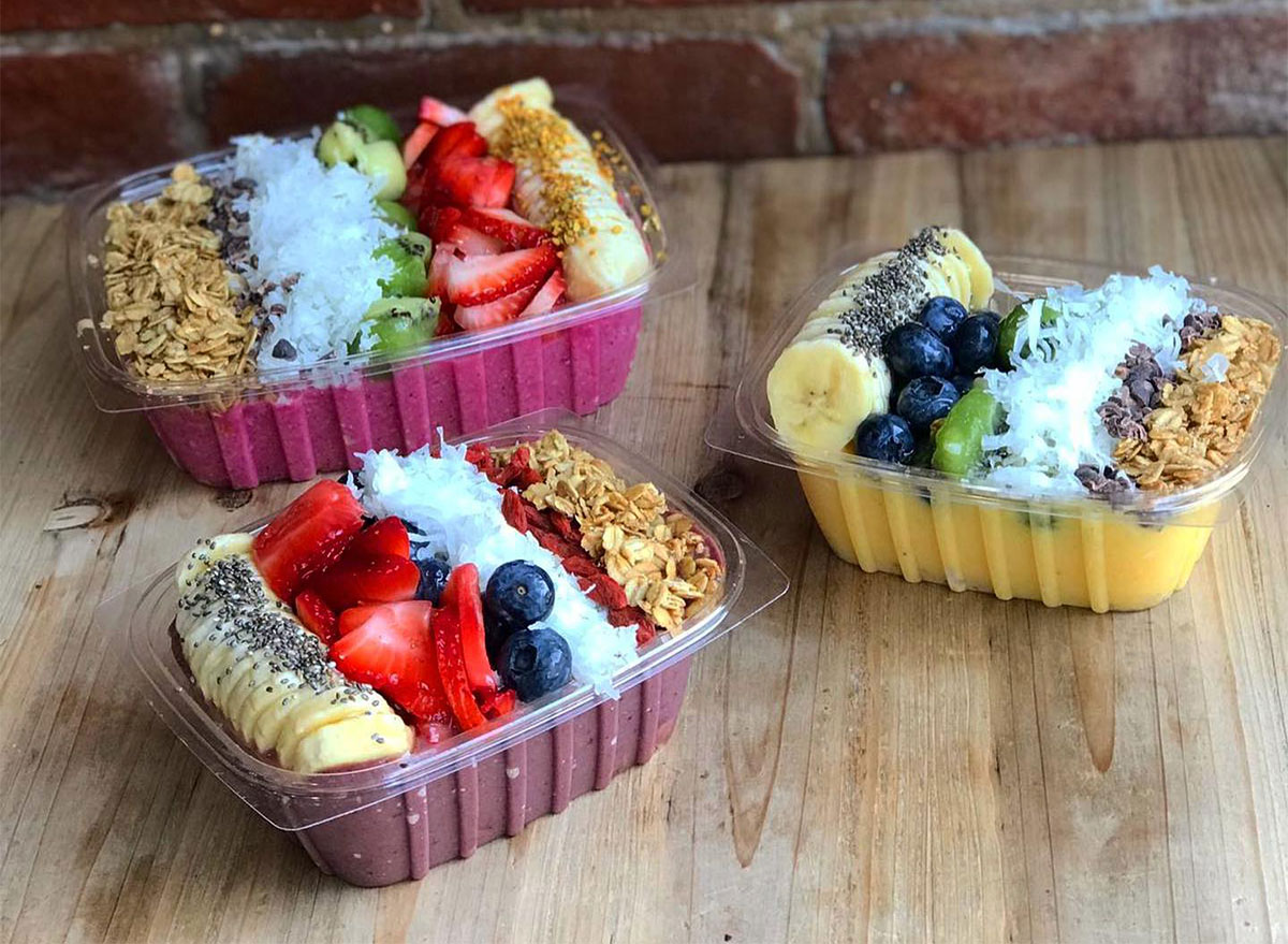 three acai bowls topped with fresh fruit