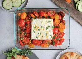 block of feta cheese in glass baking dish with tomatoes