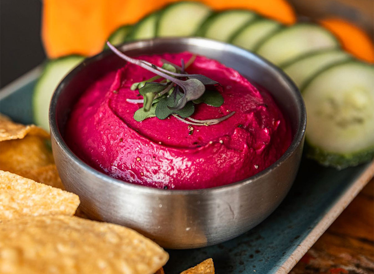 beet hummus with crackers and cucumber slices