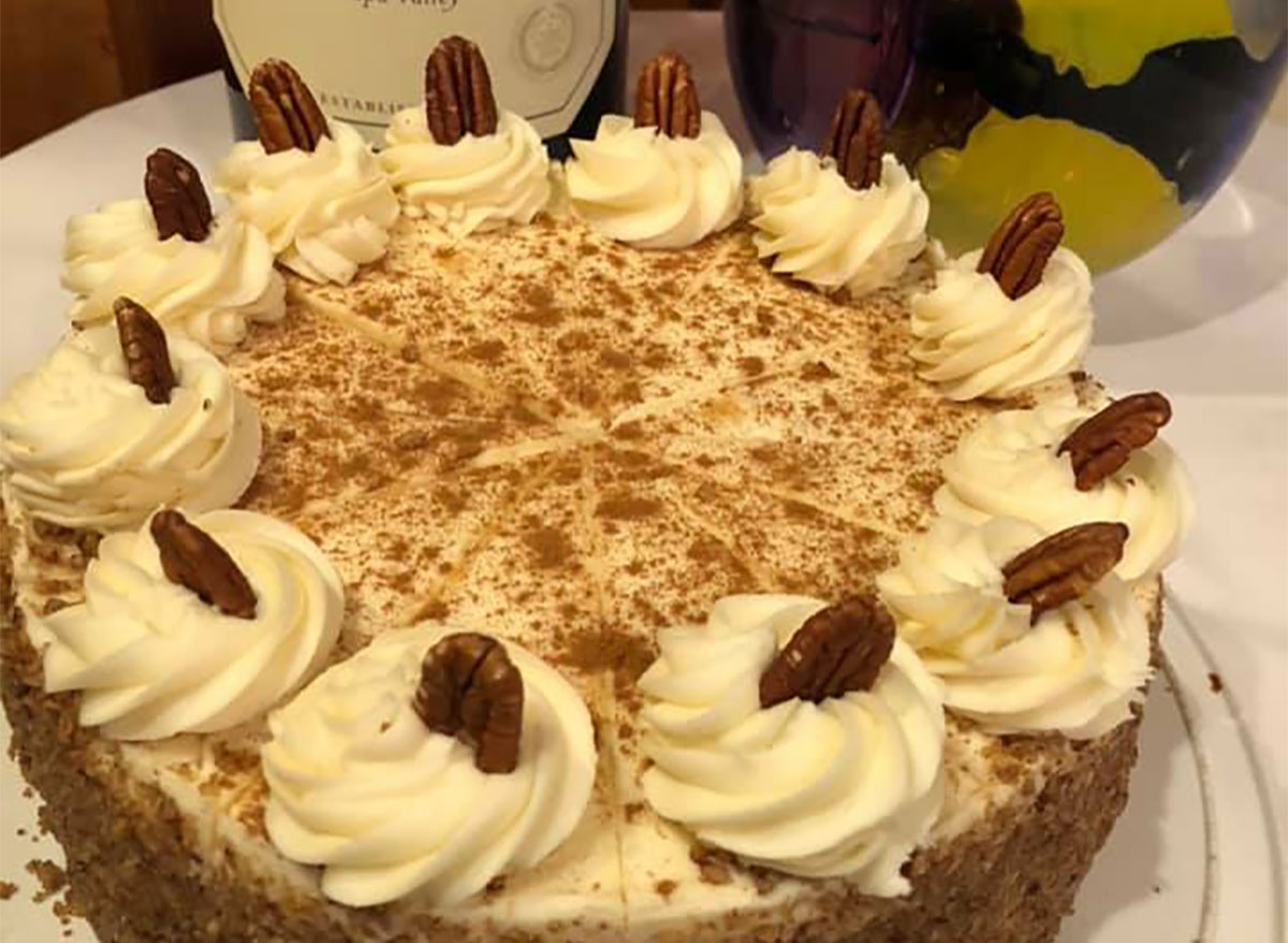 whole carrot cake topped with whipped cream and pecans