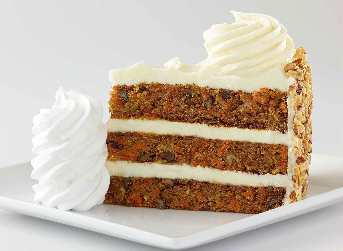 slice of carrot cake with frosting and whipped cream