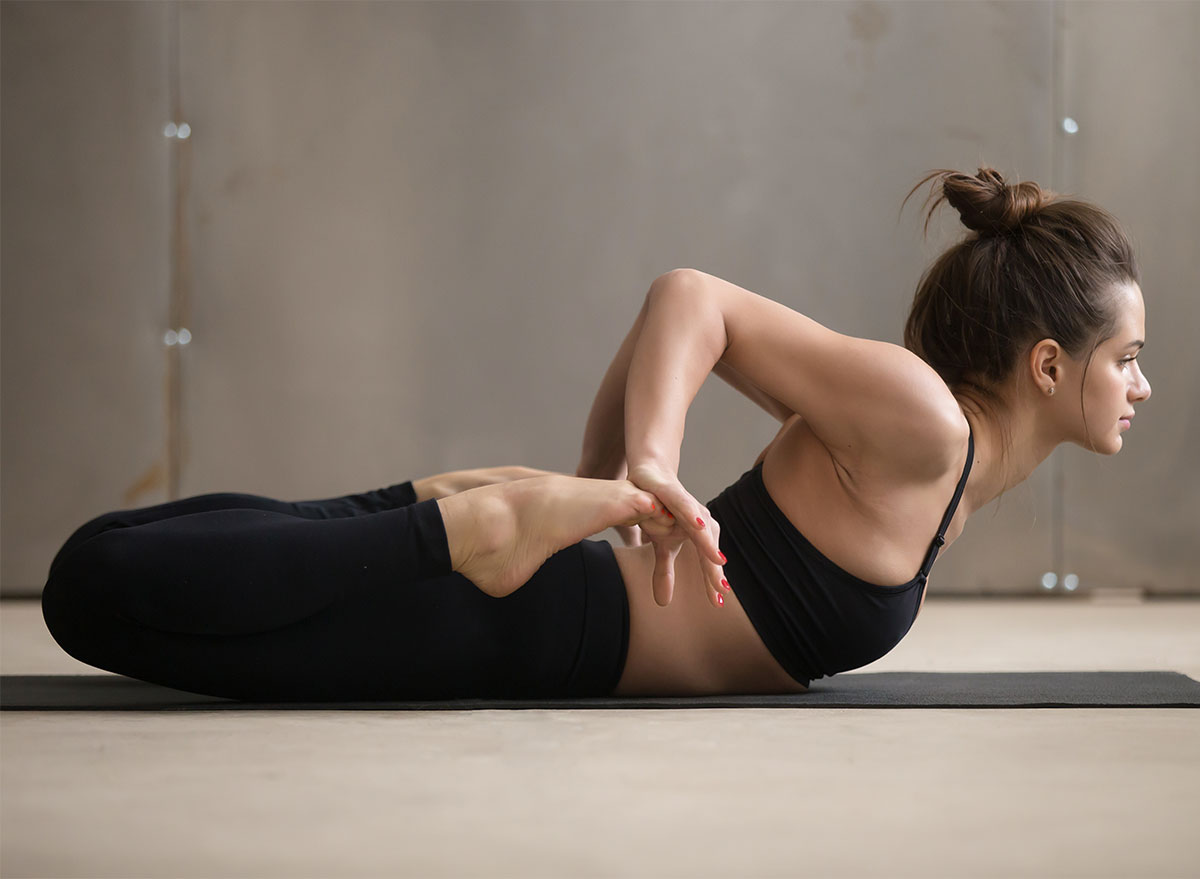 woman in black sports bra and leggings doing yoga frog stretch
