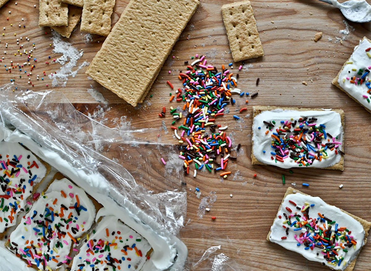 graham crackers topped with vanilla frosting and rainbow sprinkles