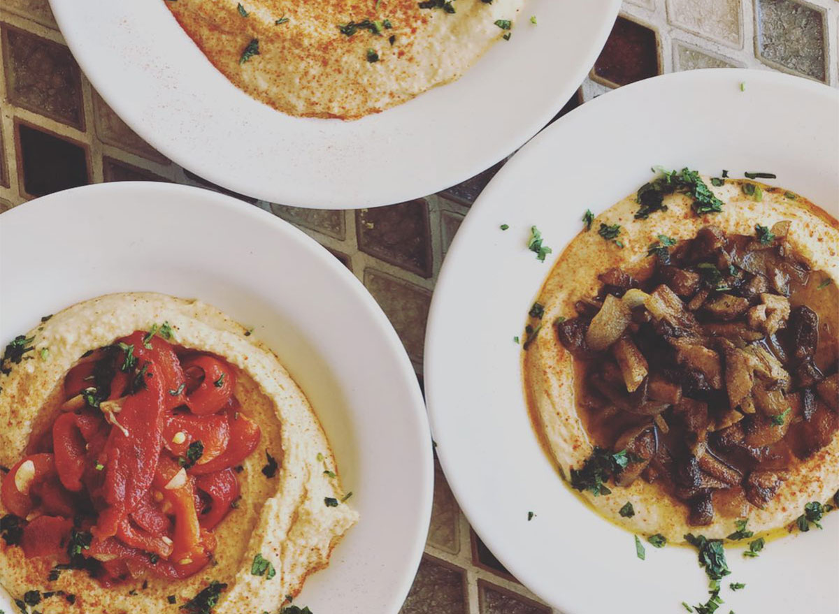 plates of hummus topped with caramelized onions and tomatoes