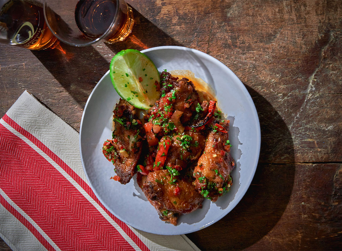 plate of chicken wings with lime wedge