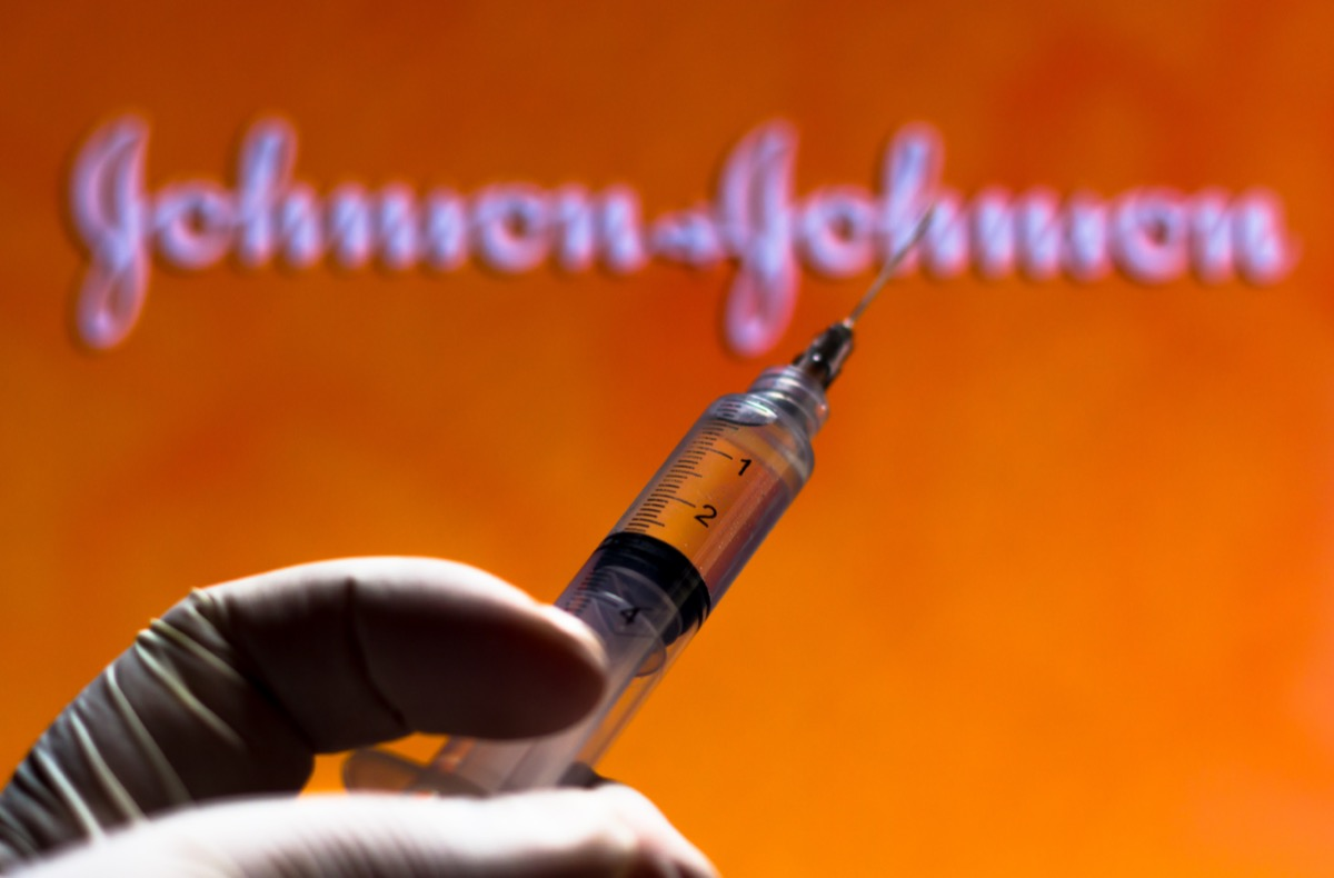 The medical syringe with Johnson and Johnson company logo displayed on a screen.
