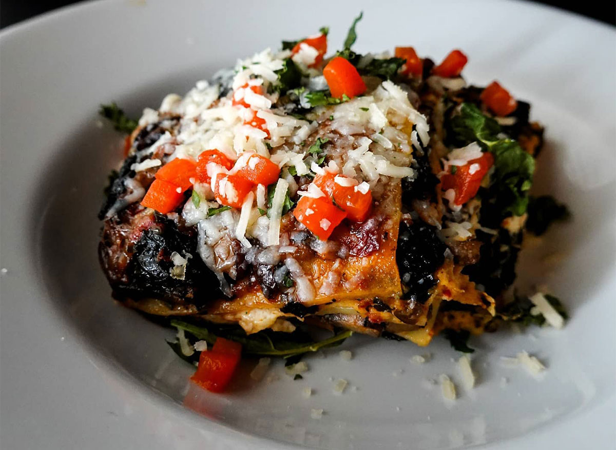 kale lasagna topped with cheese and tomatoes