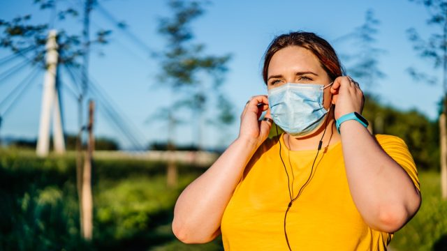 Woman with protective face mask setting music on smart phone and putting earphones before exercise.